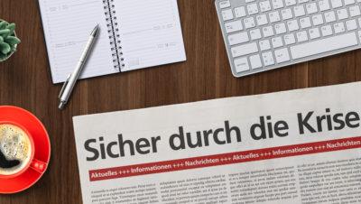 """Auf einem Schreibtisch liegt eine Zeitung mit der Schlagzeile: """"Sicher durch die Krise"""""""